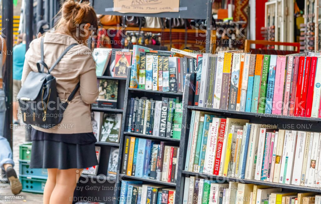 Shelves of used books on display at a second hand book shop in Camden Market with a female customer browsing in the background stock photo
