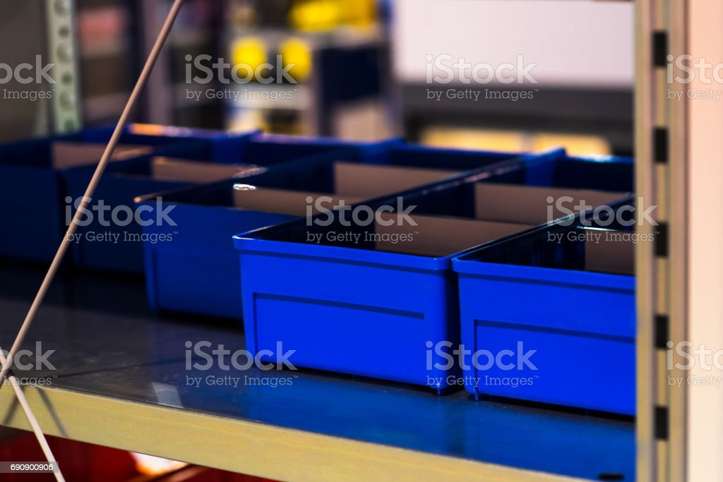 Shelving racks with empty blue boxes on a large modern warehouse stock photo