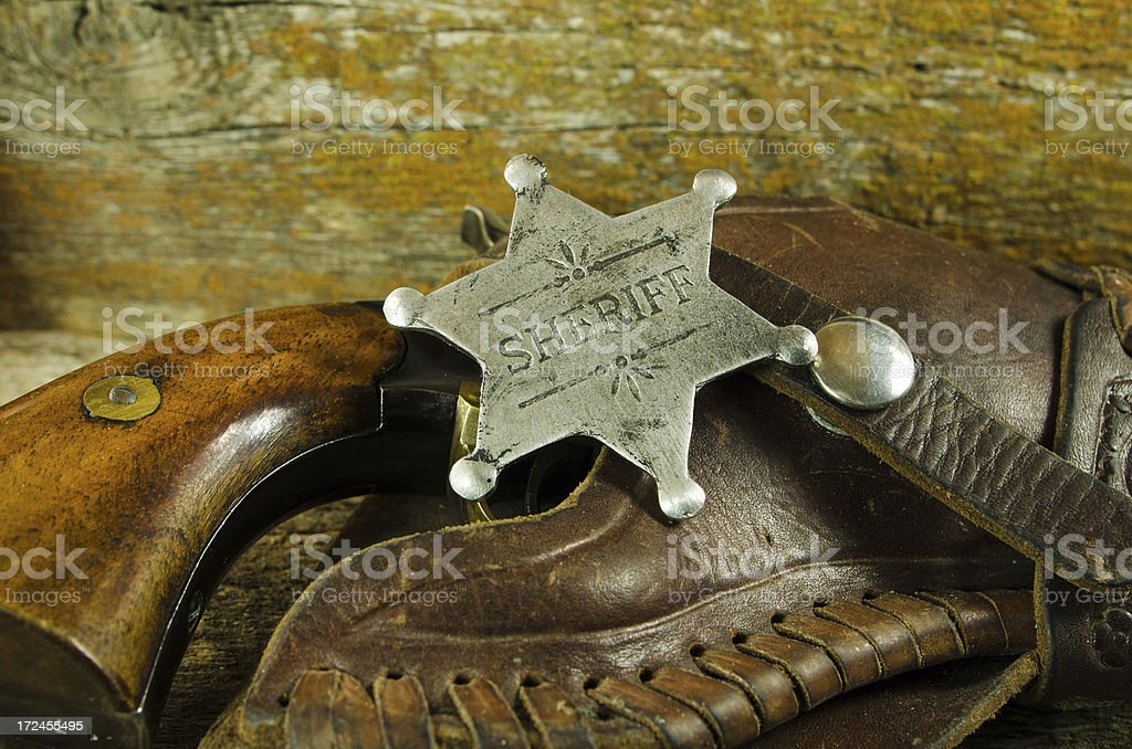Sheriff Badge and Revolver on Barn Board royalty-free stock photo