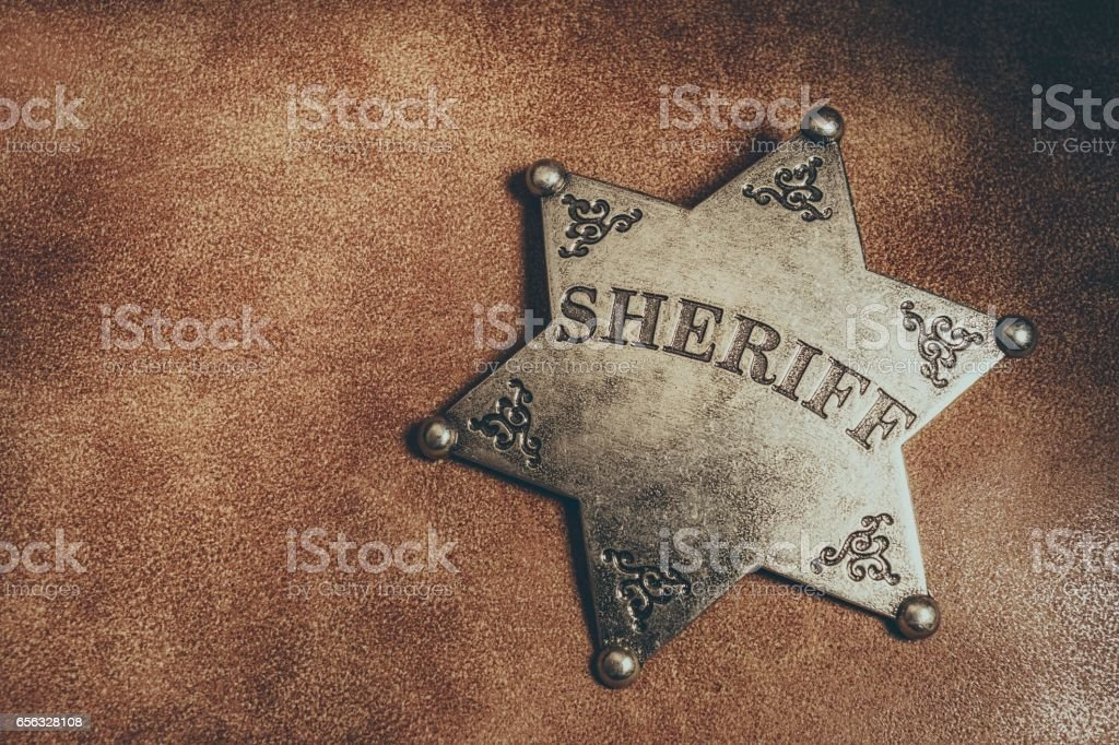 Sheriff badge on brown leather texture background. stock photo