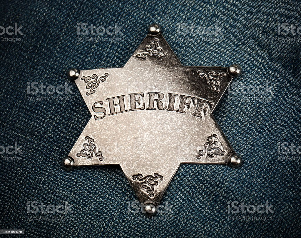 Sheriff star badge on blue denim background stock photo