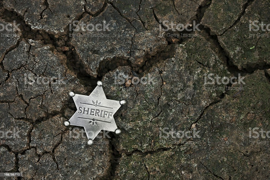 Sheriff's Star Badge on Dark Cracked Mud stock photo