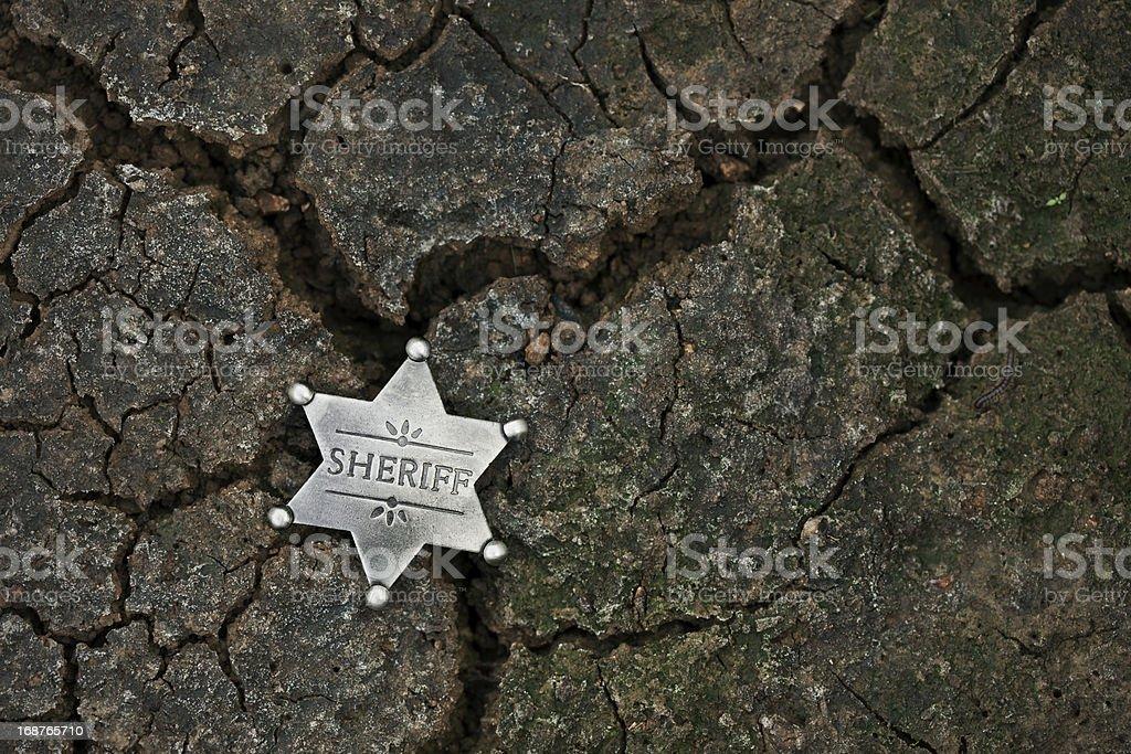 Sheriff's Star Badge on Dark Cracked Mud stock photo