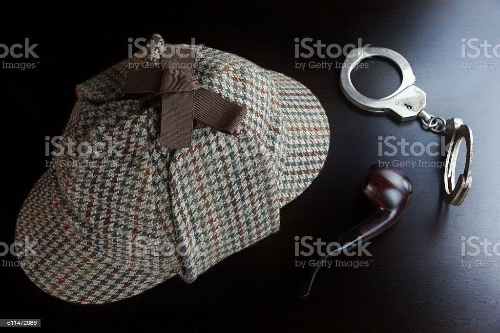 Sherlock Deerstalker Hat,  Handcuffs And Smoking Pipe On Black T stock photo