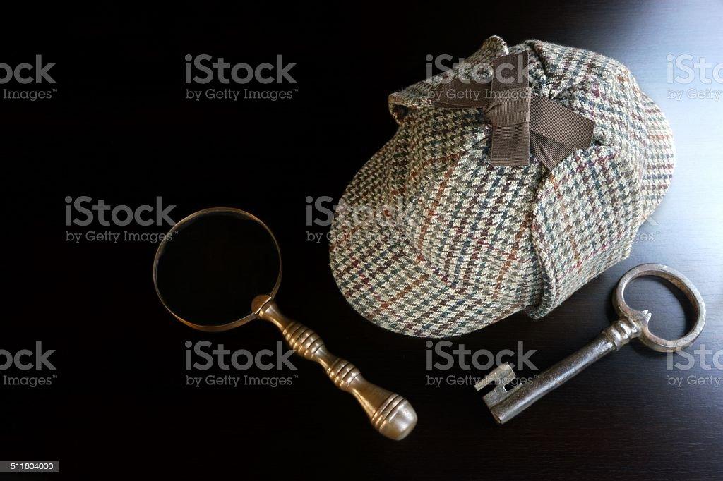 Sherlock Deerstalker Hat,  Key And Magnifier On Black Table Back stock photo