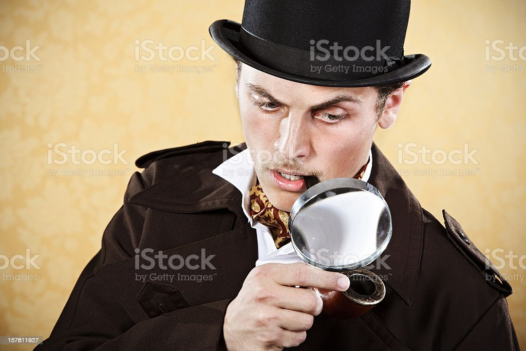 Sherlock Holmes with hat, trenchcoat, and magnifying glass stock photo