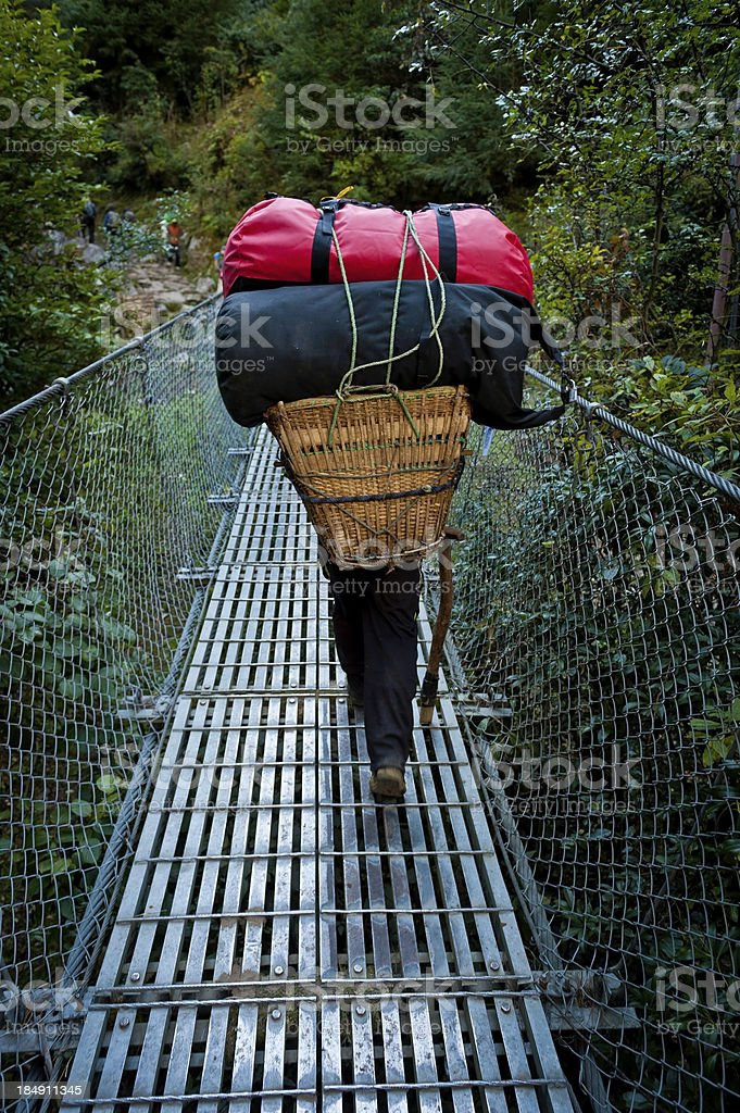 Sherpa carrying expedition bags over rope bridge Himalayas Nepal stock photo