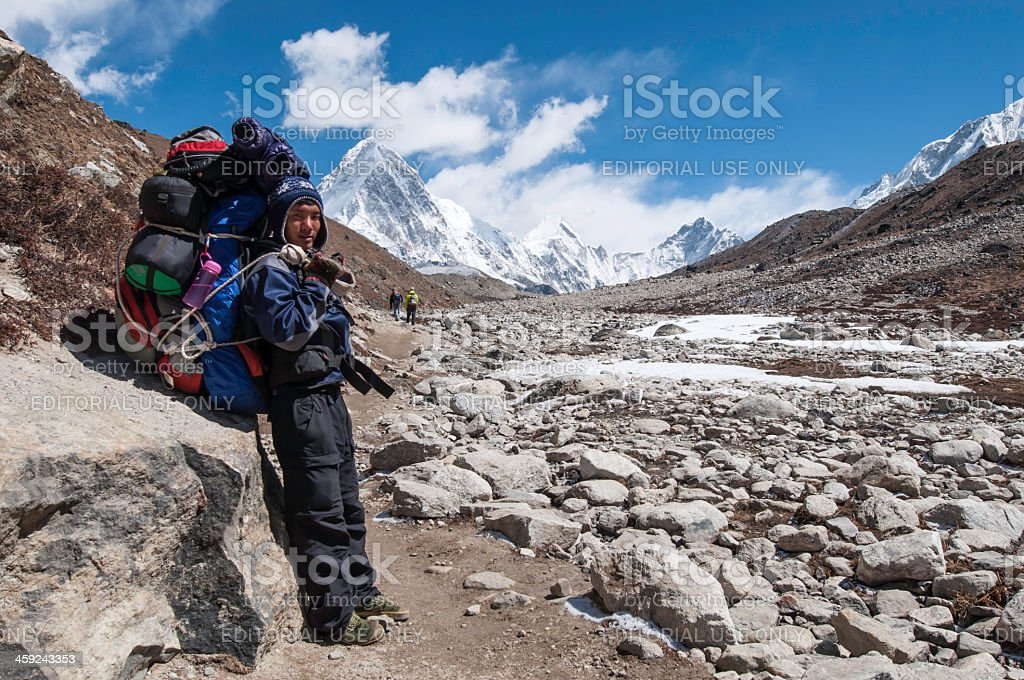 Sherpa carrying expedition kit Himalaya mountain peak Nepal stock photo