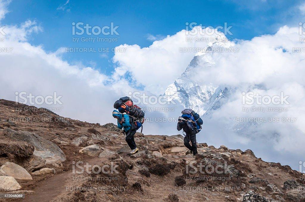 Sherpa carrying expedition kit Himalaya mountain peak Nepal royalty-free stock photo