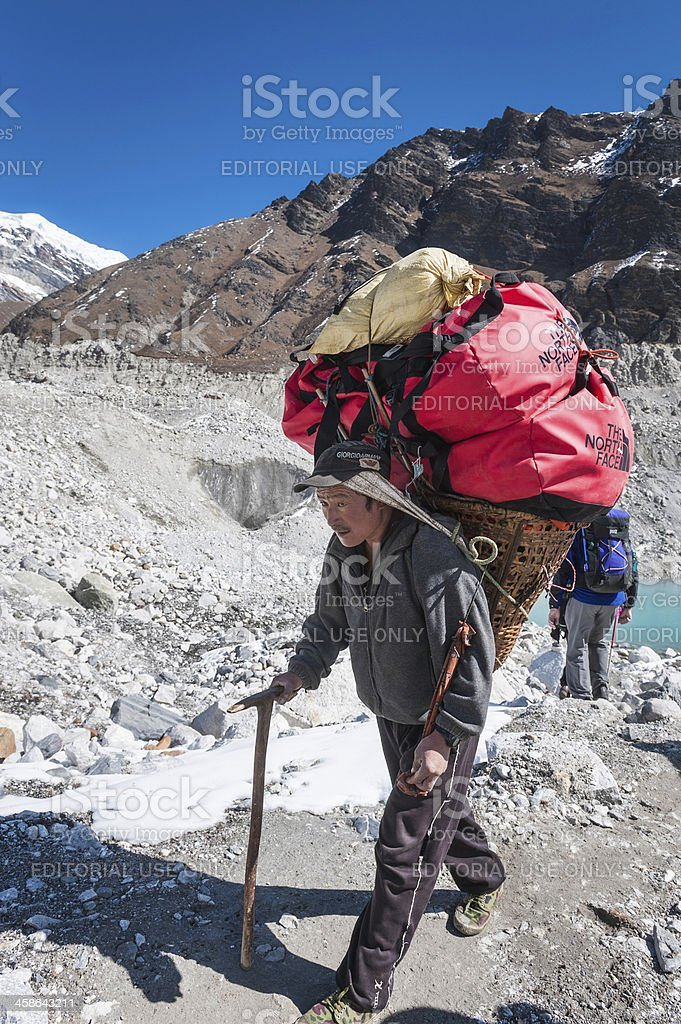 Sherpa carrying expedition kit on glacier Himalayas stock photo