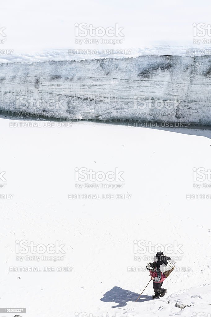 Sherpa carrying load across glacier Himalayas royalty-free stock photo