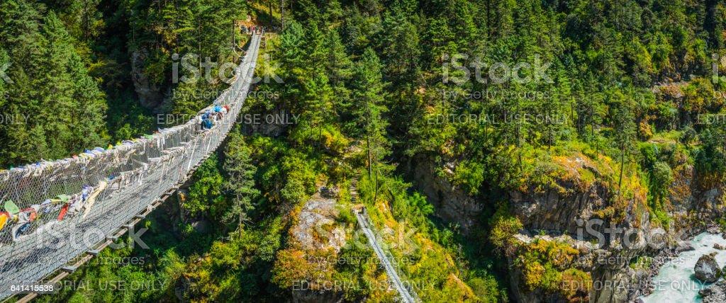 Sherpa crossing highwire rope bridge over mountain canyon Himalayas Nepal stock photo