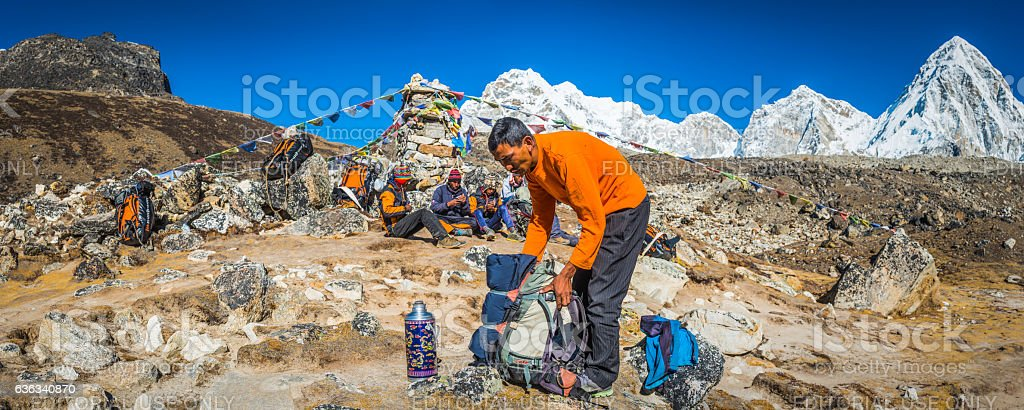 Sherpa guide and porters beside prayer flags Himalaya mountains Nepal stock photo
