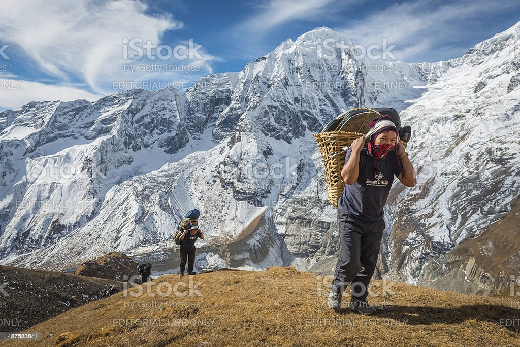 Sherpa mountaineers carrying heavy expedition loads high in Himalayas Nepal stock photo