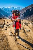 Sherpa porter carrying doko bamboo basket Himalaya mountain trail Nepal