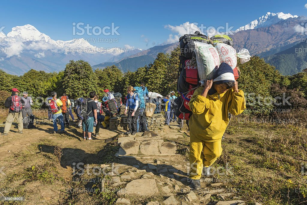 Sherpa porter carrying expedition kit in Himalayas Nepal royalty-free stock photo