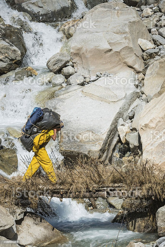 Sherpa porter carrying expedition kit over mountain river Himalayas Nepal stock photo