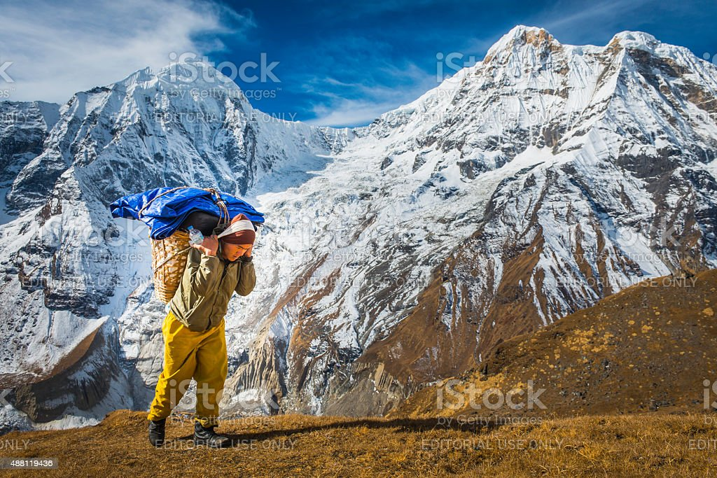 Sherpa porter carrying expedition kit to base camp Himalayas Nepal stock photo