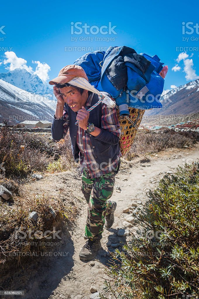 Sherpa porter carrying heavy basket along trail Himalayas Nepal stock photo