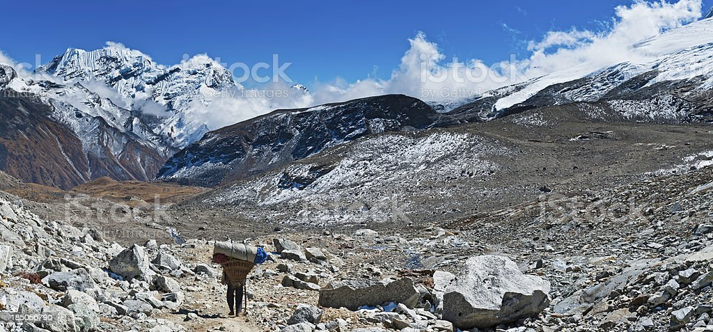 Sherpa porter carrying heavy load Himalayas Nepal stock photo