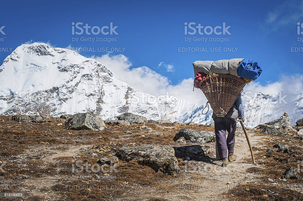 Sherpa porter carrying heavy load in traditional basket Himalayas Nepal stock photo
