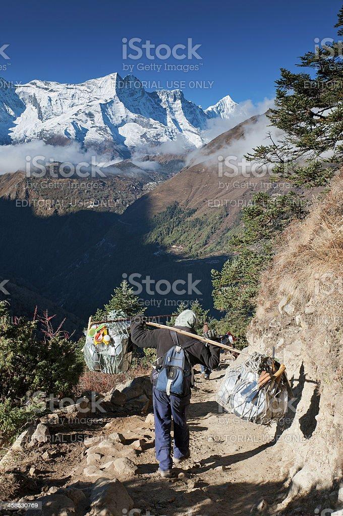 Sherpa porter carrying kitchen equipment Himalayas Nepal stock photo