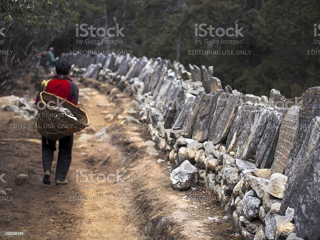 Sherpa Porter Walking Next to Mani Stones stock photo