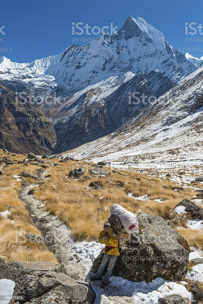 Sherpa porter with basket resting under Machapuchare Himalayas Nepal royalty-free stock photo