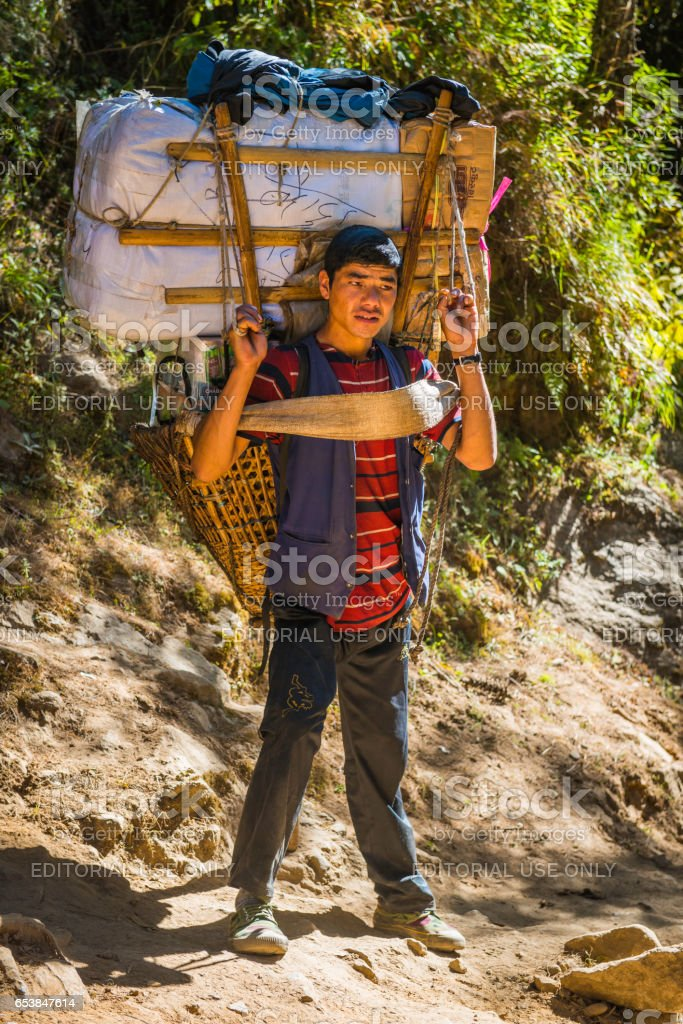 Sherpa porter with traditional bamboo basket in Himalayan mountains Nepal stock photo