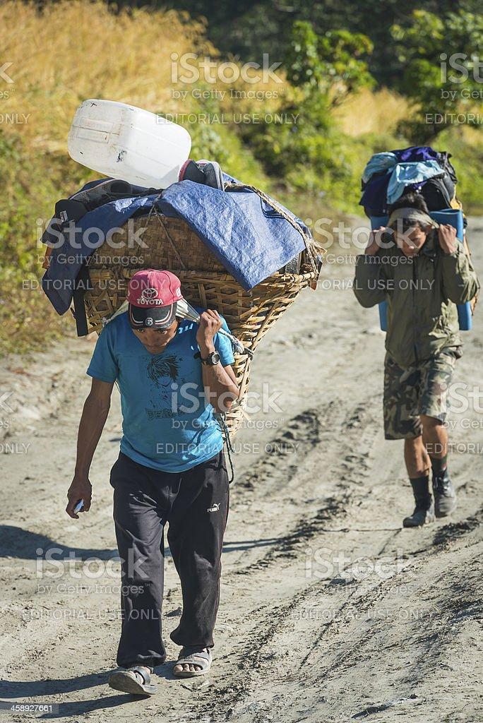 Sherpa porters carrying expedition kit Annapurnas Himalayas Nepal royalty-free stock photo