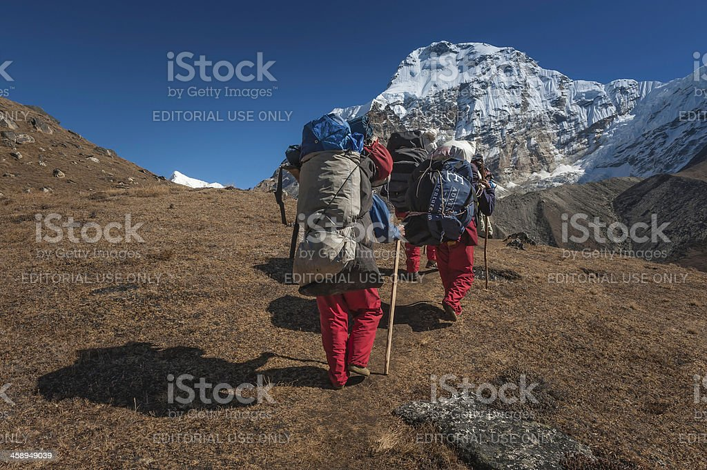 Sherpa porters carrying expedition kit Himalayas Nepal stock photo