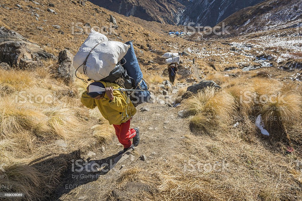 Sherpa porters carrying heavy expedition loads in Himalayas Nepal royalty-free stock photo