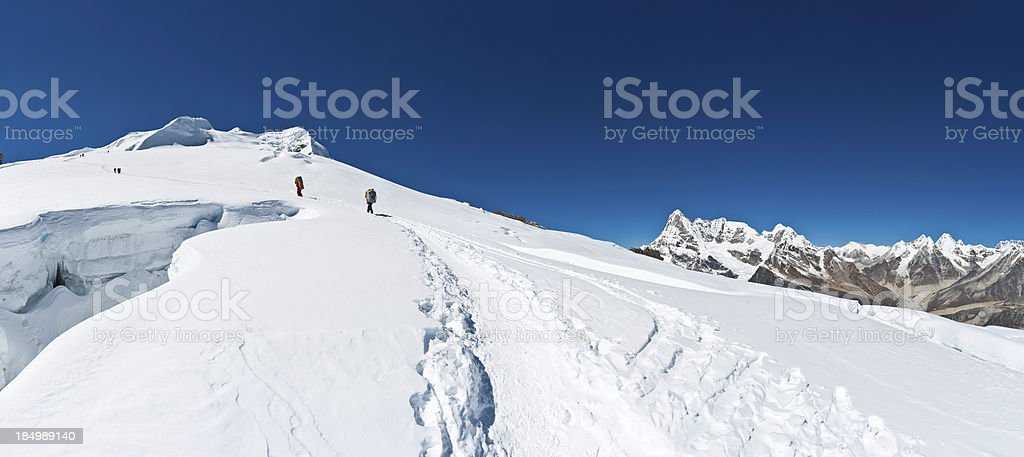 Sherpa porters climbing mountain glacier Himalayas stock photo