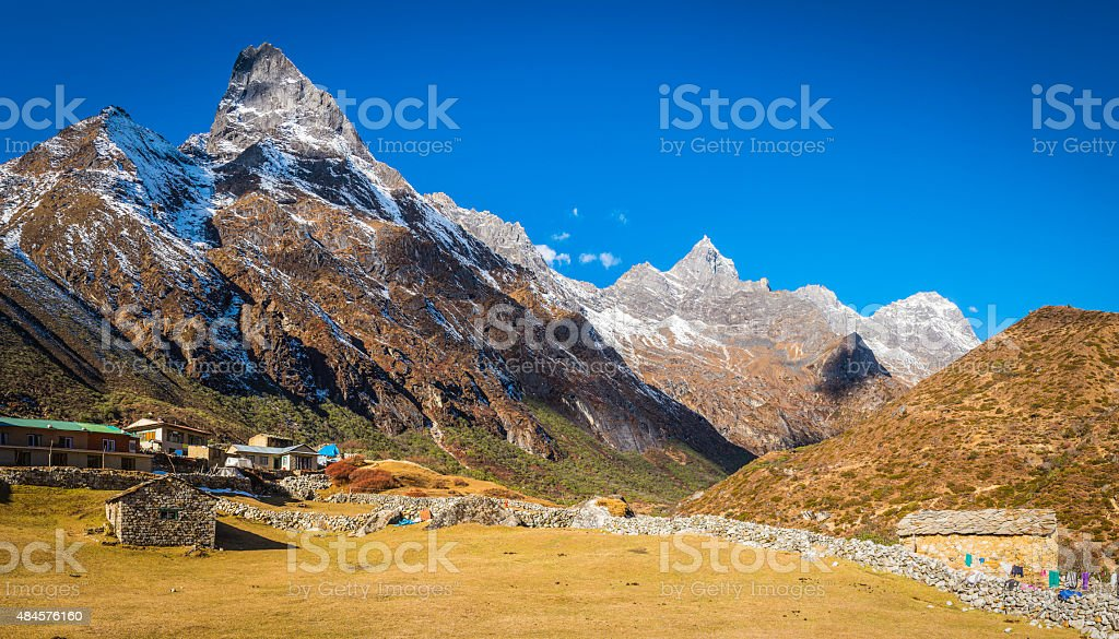 Sherpa teahouses village lodges beneath Himalayan mountain peaks panorama Nepal stock photo