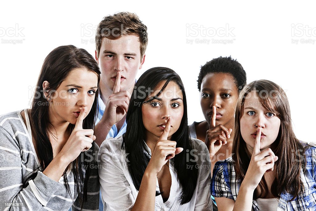 Shhh!  Five young people with fingers to lips stock photo
