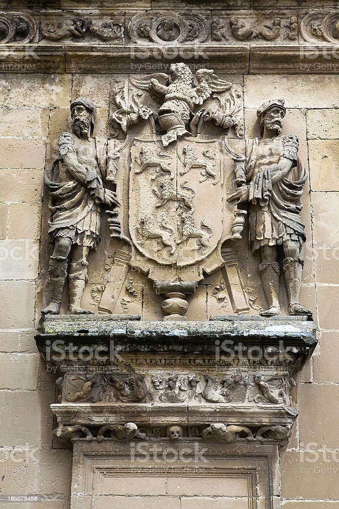 Shield of stone framed by two men stock photo