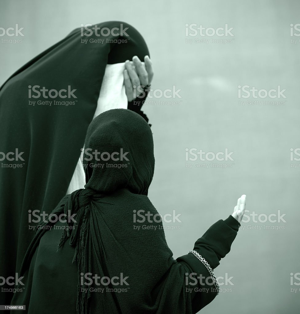 Shiite Muslim woman and young girl are praying. stock photo