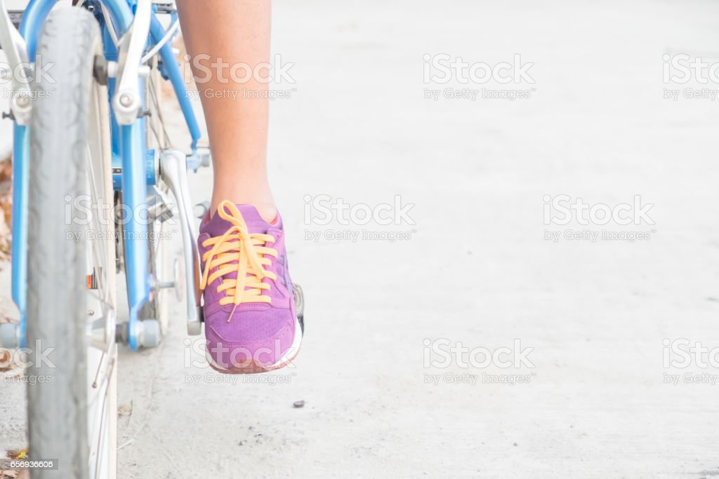 shin of woman and purple shoes on blue bicycle with empty copy space for background. stock photo