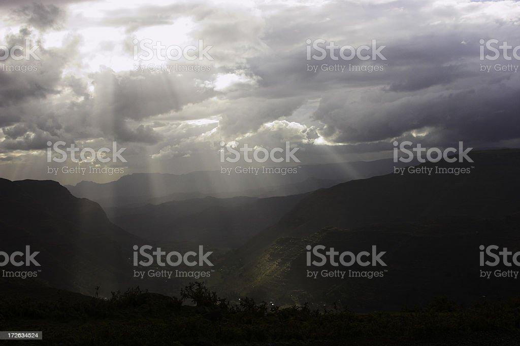 Shining light through a dark sky stock photo