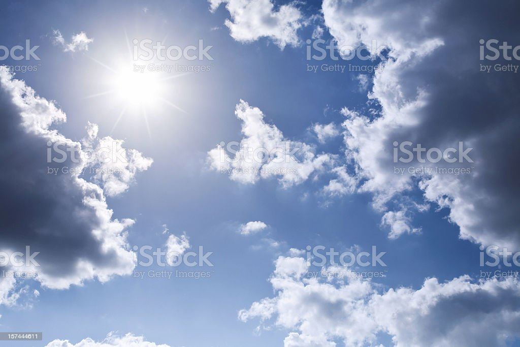 Shining Sun framed by clouds on a blue sky royalty-free stock photo
