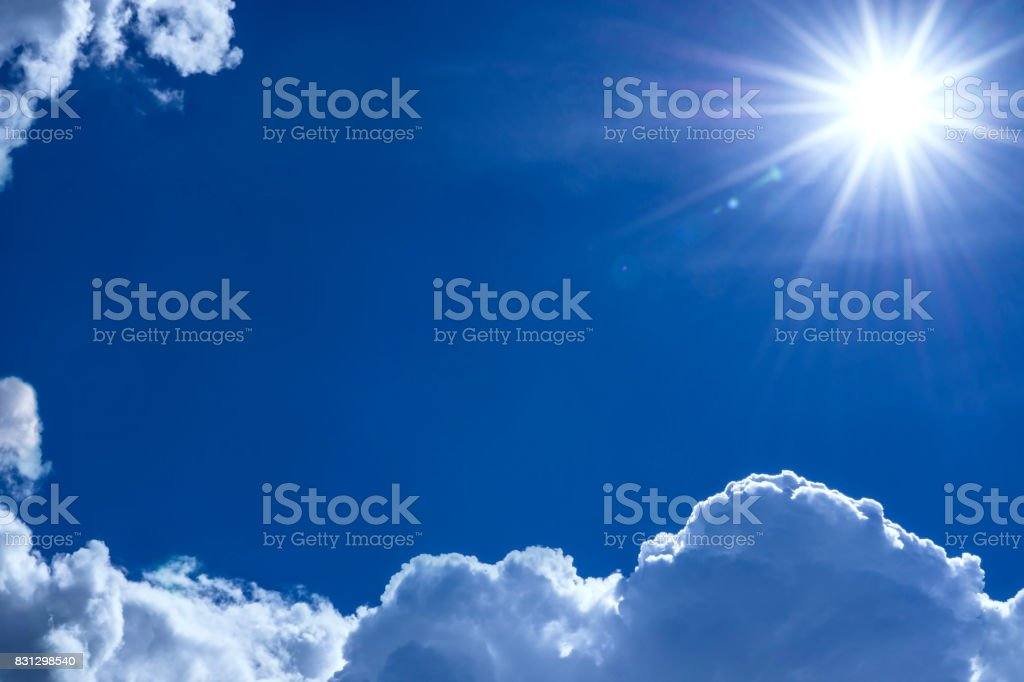 Shining sun on blue sky with white clouds stock photo