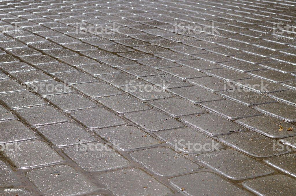 Shining wet rectangular tiled stone pavement in diagonal layout stock photo