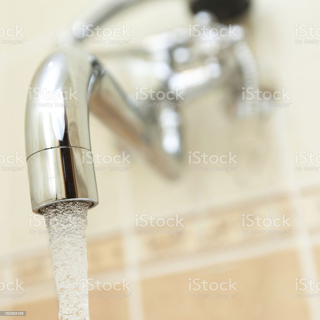 Shinny faucet attached to a wall royalty-free stock photo