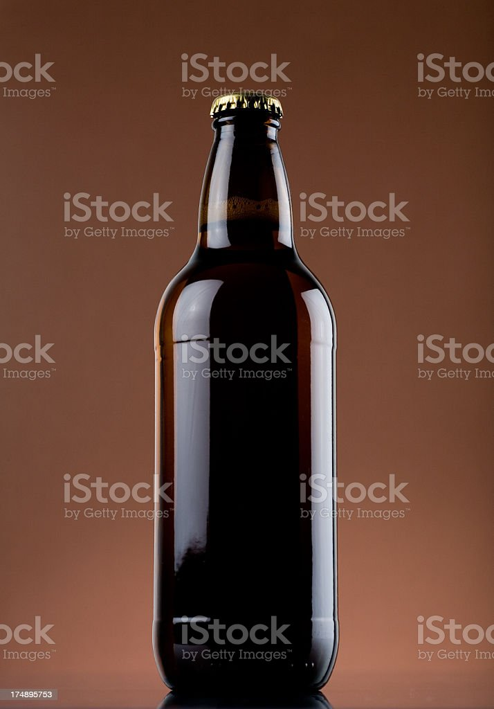 Shiny beer bottle on a tan background stock photo