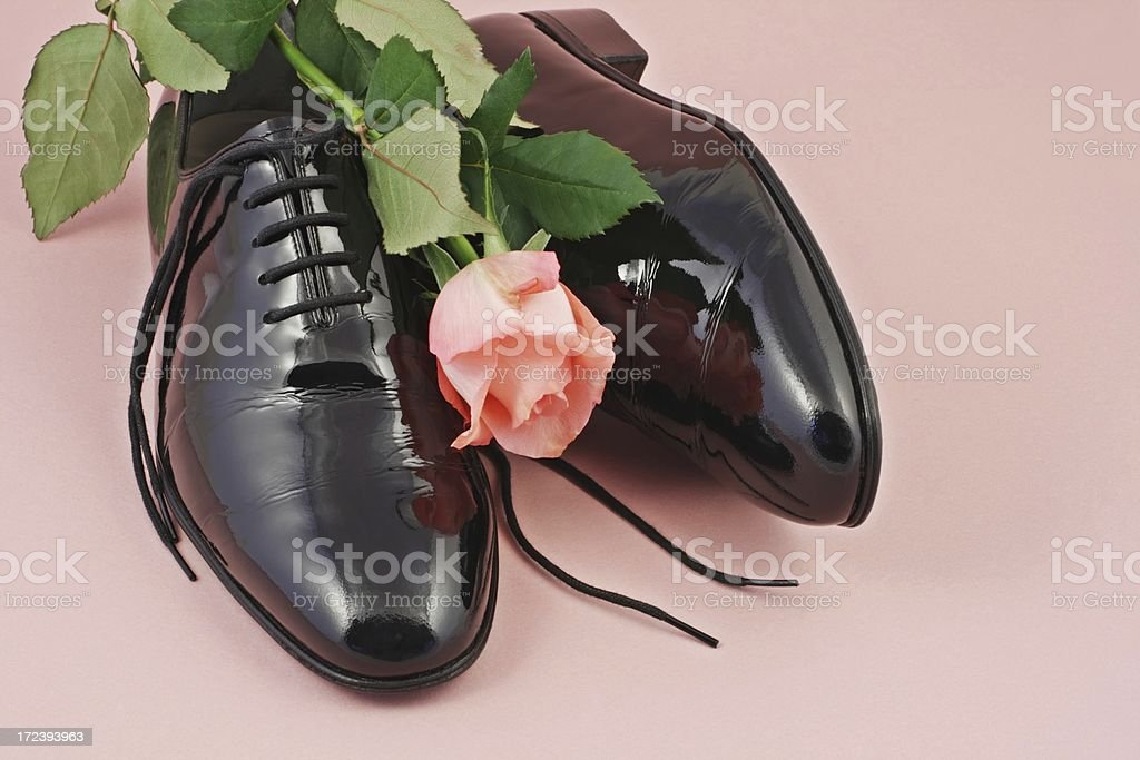 Shiny black male patent leather shoes and  a red rose. royalty-free stock photo