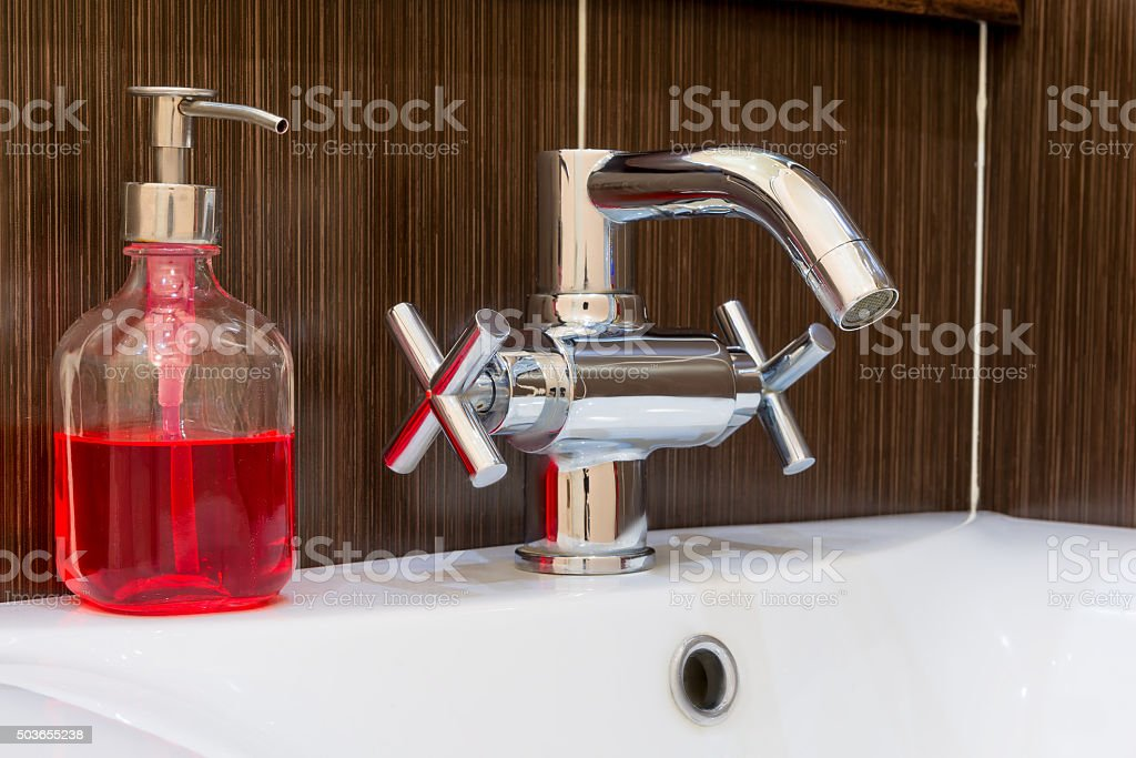 shiny faucet and soap dispenser in the bathroom close up stock photo