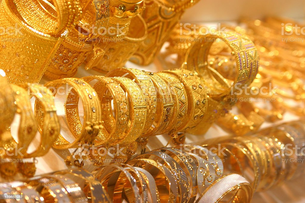Shiny gold bangles and cuffs on display royalty-free stock photo