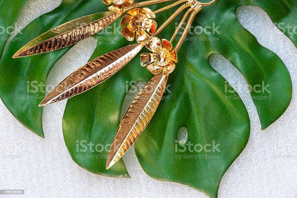 Shiny gold flower on green leaf royalty-free stock photo