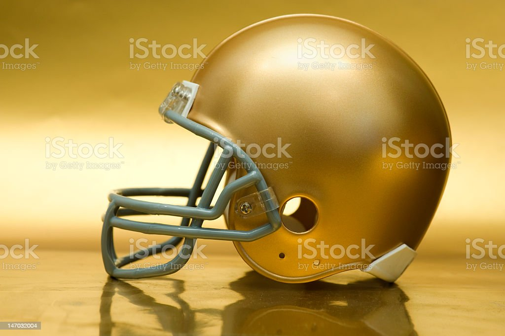 Shiny golden American football helmet on golden surface stock photo