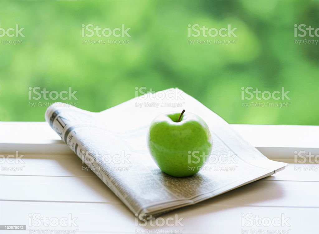A shiny green apple on top of a newspaper royalty-free stock photo